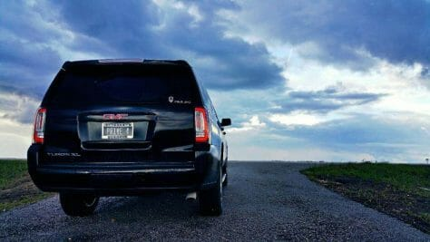 Picture of a GMC Yukon XL from the back with a scenic background while the sun is setting.