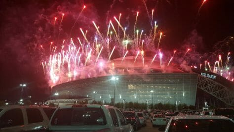 Picture of the AT&T Stadium in the evening with red fireworks shooting out of it.