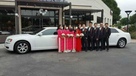 Bridal party with bride in groom in front of white limo during the day