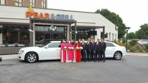 Bridal party outside of hotel restaurant  posing in front of white limo during the day