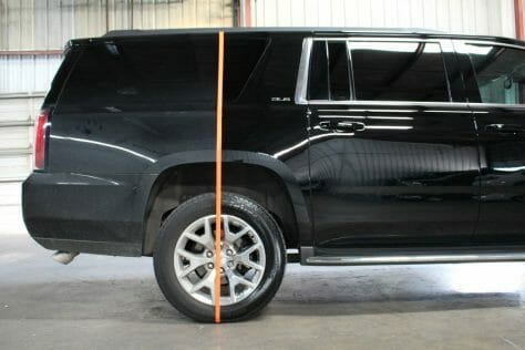 Orange tape on the rear of a black Yukon XL  separating a very dirty and a very clean area