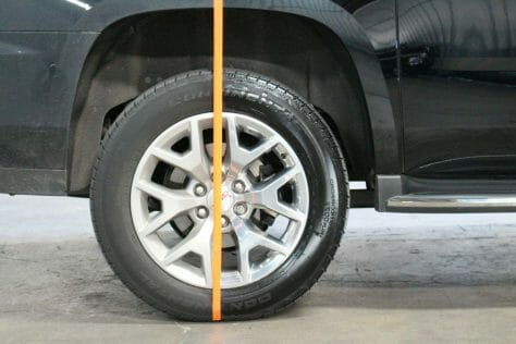 Orange tape separating a tire with a very dirty side and a completely clean side on a black Yukon XL