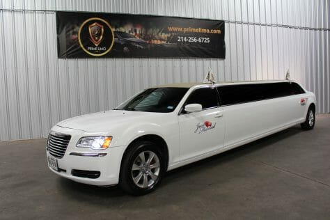 White Chrysler 300 limo with Just Married Signs and flags