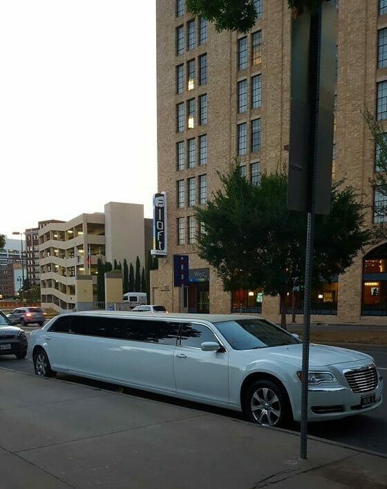 White Chrysler 300 limo outside Pioneer Plaza with building in the back during the day