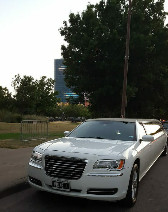 Front of white Chrysler 300 limo outside Pioneer Plaza during the day