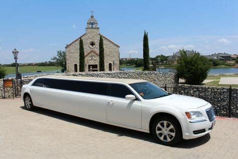 White Chrysler 300 limo in front of a church on a bright sunny day